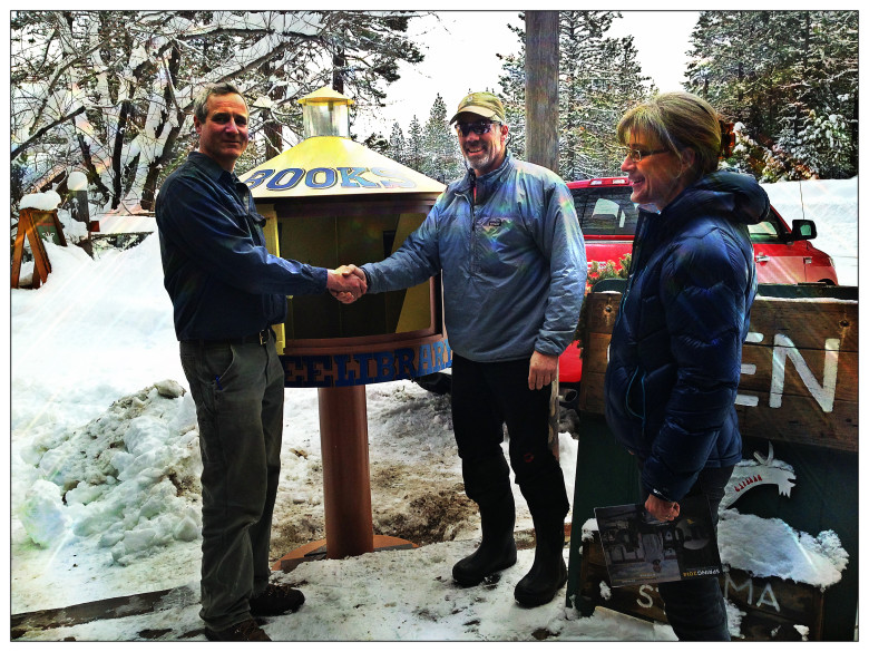 Artist Tim Odell (left) shakes hands with Mazama Store owner Rick Leduc. Missy Leduc watches as the Little ART Library was installed, Tues, Mar 4th.